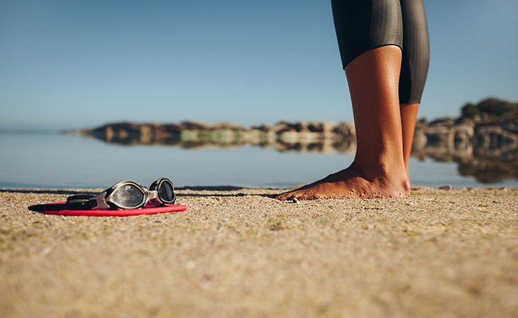 Swim goggles on the sand with feet of a woman standing by. Focus on goggles.